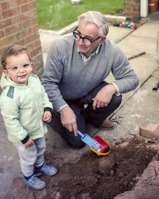 Grandparent digging in sand pit